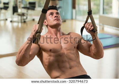 Attractive Man Does Crossfit Push Ups With Trx Fitness Straps In The Gym's Studio