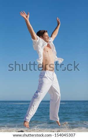 Attractive man jumping on beach against sea on a sunny day