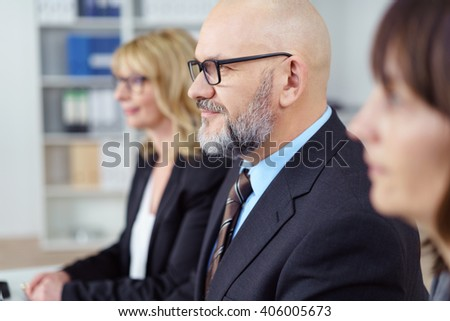 Attractive senior businessman with a shaved head and glasses seated in a meeting listening with a serious expression, close up selective focus between two women
