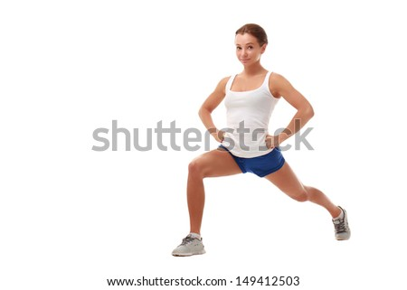 Attractive slim female fitness model performing a stretching exercises. Caucasian, brown hair, brown eyes, 20 - 30 years old, young.