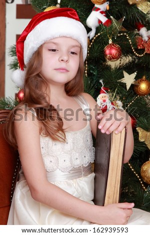 Attractive smiley little girl holding dark brown vintage book over Christmas decoration on Holiday theme/Cheerful young girl wearing santa's hat and holding big ancient book