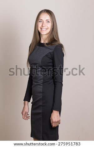 Attractive smiling young woman in a black dress looking at camera.