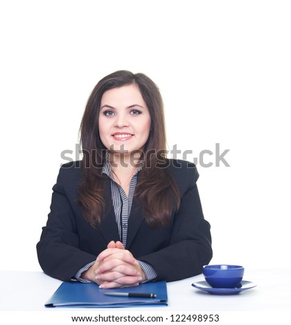 Attractive smiling young woman in a black jacket and blouse sitting at the table. On the table lay a pen, blue folder, a cup and saucer. Isolated on white background