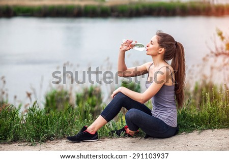 Attractive Sporty Young Woman drinking Water from a bottle after jogging or running