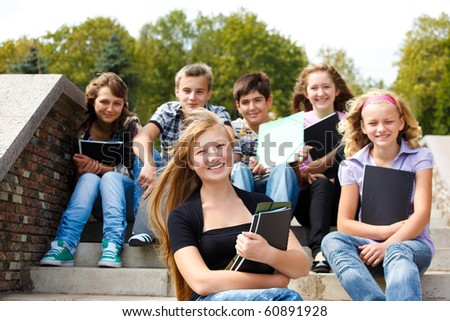 Attractive teenagers with books laughing