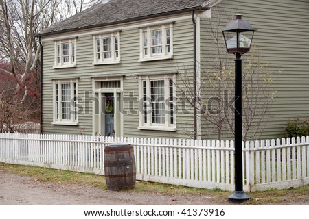 Attractive, well maintained, pioneer house behind white picket fence and lamp post