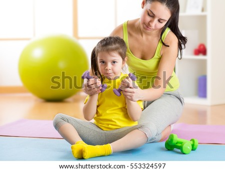 Attractive woman and her child girl exercising with dumbbells
