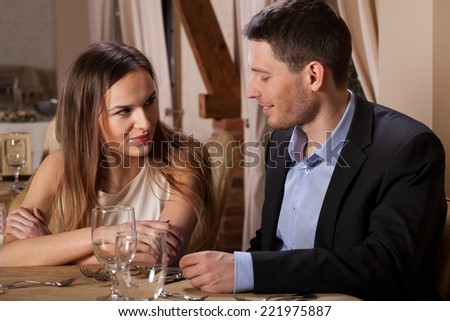 Attractive woman coquetting her friend during meeting in restaurant