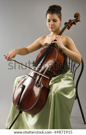 Attractive woman in evening dress playing cello