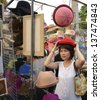 Attractive woman trying on a hat at a street fair in Chiang Mai,Thailand - stock photo