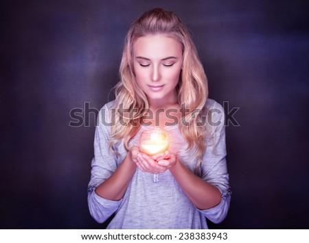 Attractive woman with candle on dark background, calm girl with closed eyes praying, Christmas holidays concept