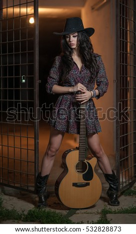 Attractive woman with country look, indoors shot, american country style. Girl with black cowboy hat and guitar. Beautiful brunette with short dress and boots posing fashion indoors with a guitar