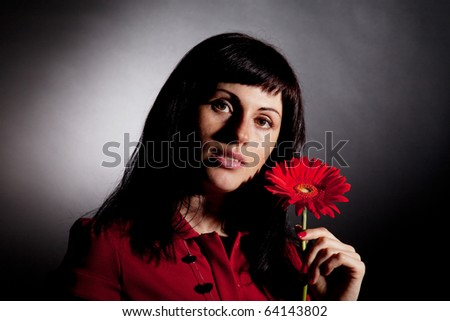 Attractive woman with red flower on black background