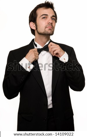 Attractive young brunette man with a beard wearing a black tuxedo fixing bow tie standing on white