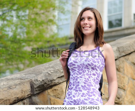 Attractive young brunette woman (Caucasian) in a purple and white tank top - walking down stairs with a backpack