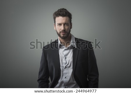 Attractive young businessman posing on gray background