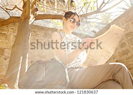 Attractive young businesswoman reading a financial newspaper while sitting down on a stone wall in a park with direct sun rays filtering through.