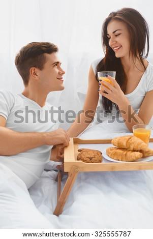Attractive young couple having a romantic breakfast in bed in the morning. Relationships, love, care.