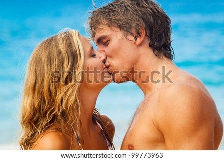 Attractive Young Couple Kissing on Tropical Beach