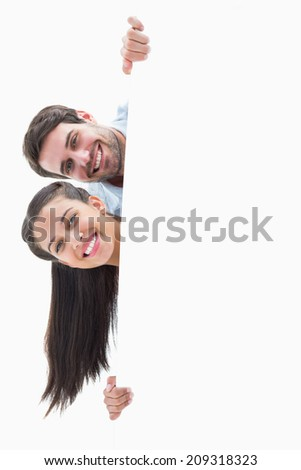 Attractive young couple smiling at camera on white background