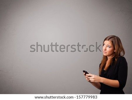 attractive young lady standing and holding a phone with copy space