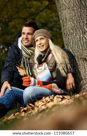 Attractive young loving couple sitting on ground by tree in autumn park, smiling.