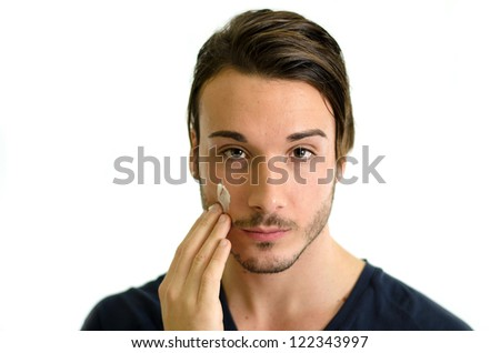 Attractive young man applying moisturizing cream or lotion on face skin