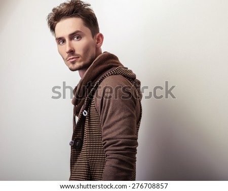 Attractive young man in a brown sweater pose in studio.