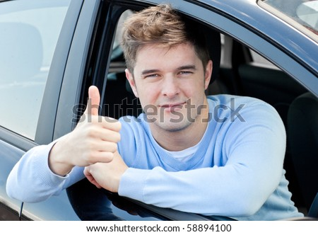 Attractive young man sitting in his car with thumb up smiling at the camera