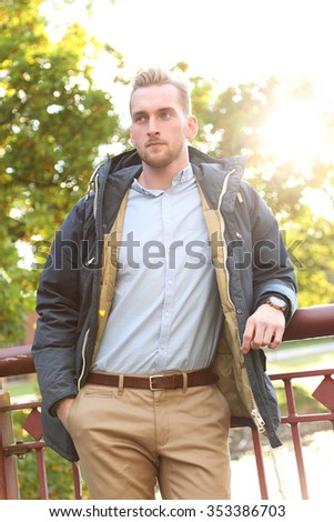 Attractive young man standing on a bridge wearing a jacket and shirt on a cold autumn day, with a nice big lens flare behind him. Sunny day.