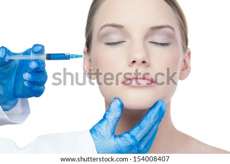 Attractive young model on white background having an injection on the cheek