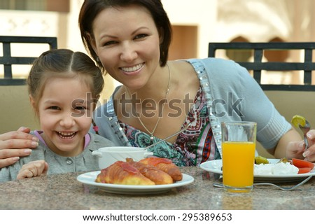 Attractive young mother with daughter at breakfast on tropical resort