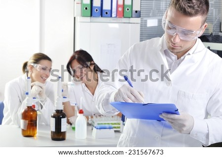 Attractive young PhD student scientist with two colleague out of focus behind him in chemical laboratory