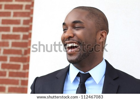 Attractive, Young Professional African American Businessman Smiling and Laughing  While Looking to the Side and Wearing a Black Suit and Tie