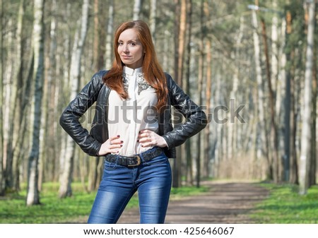 Attractive young redhead woman in spring park in sunny day