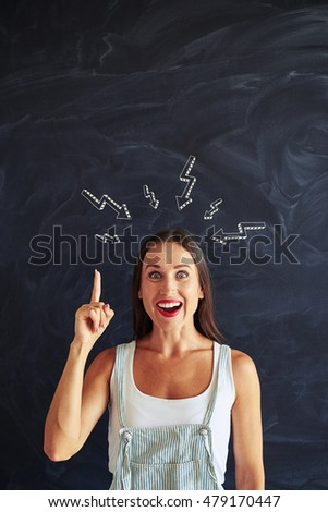 Attractive young woman against blackboard background is having brainstorm