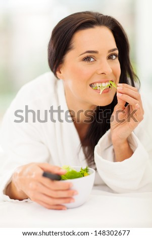 attractive young woman eating salad on bed