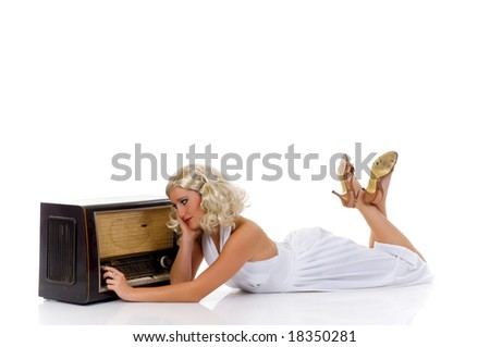 Attractive young woman in classy white dress next to retro radio. Studio shot, white background.