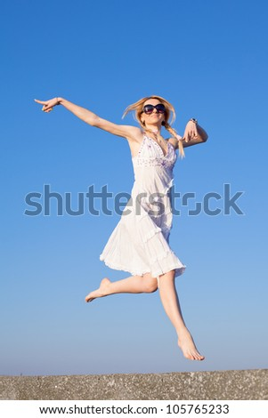 Attractive young woman in white sundress running on background of sky. Barefoot girl in sunglasses on open air