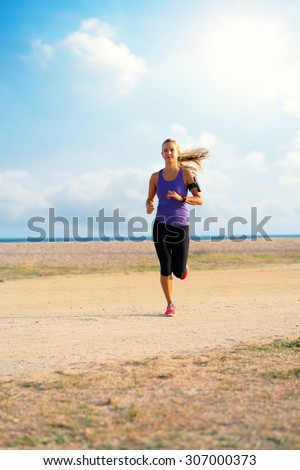 Attractive young woman running with smart watch and armband along beach in early morning sun.