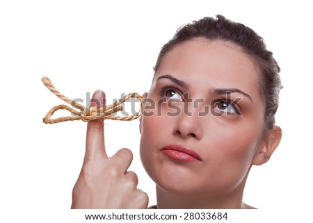 Attractive young woman trying to remember what the piece of string round her finger was meant to remind her of, isolated on white background.