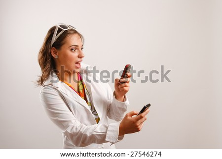 Attractive young woman wearing white jacket looking at the cellphone