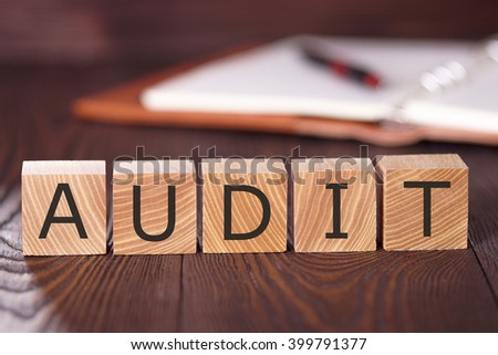 Audit. The word audit is written on wooden blocks. Cubes with inscription audit on old boards. Close-up.