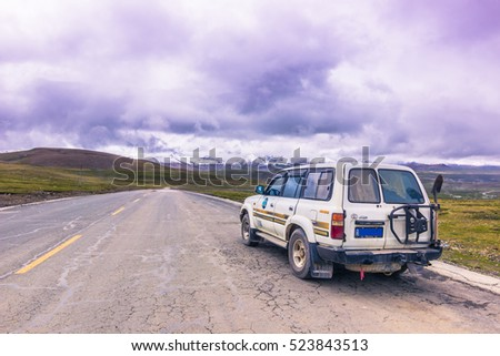 August 16, 2014: A touristic tour car crossing the vastness of the Tibetan Plateau