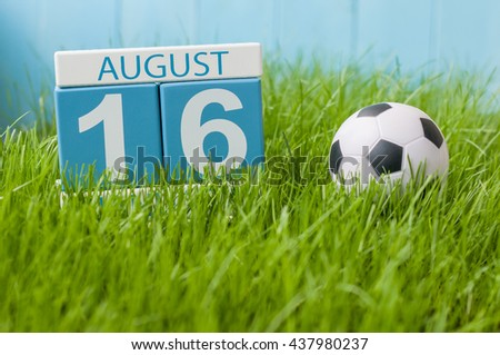 August 16th. Image of august 16 wooden color calendar on green grass lawn background with soccer ball. Summer day. Empty space for text
