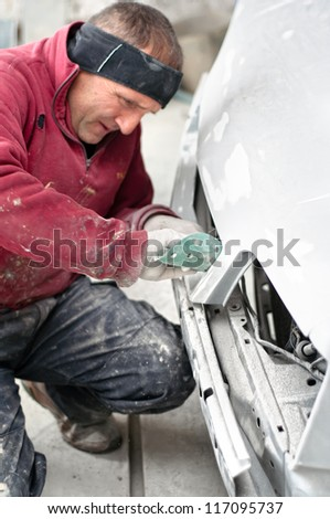 Auto mechanic preparing a car for a new paint job
