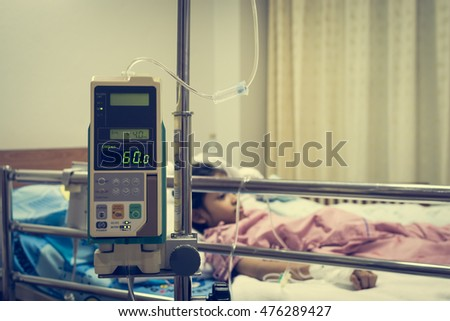 Automatic infusion pump and IV hanging on a pole with kid patient in hospital