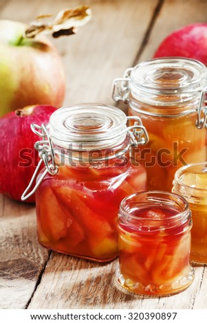 Autumn apple jam ripe red apples in jars on an old wooden table, selective focus