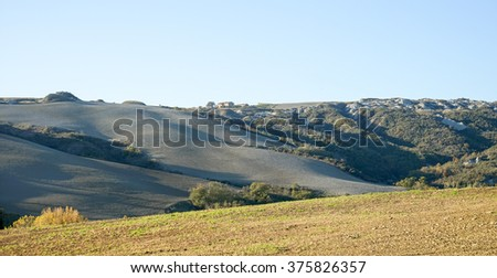 Autumn in Italian Toscana, fields on the hills with farm hous in the backgroung