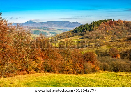 Autumn mountain landscape. trees and meadow strewn with foliage in the foreground. small village can be seen away in the mountains